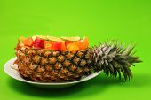 foto of green papaya salad  - Thai style fruit salad inside a pineapple with a green background - JPG