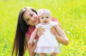 picture of mother baby nature  - Sunny portrait of happy young mother with baby on the grass in summer warm day - JPG
