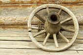 stock photo of wagon wheel  - The old wagon wheel against the wall farmhouse - JPG