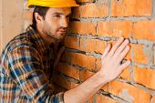 picture of concentration man  - Concentrated young man in hardhat touching brick wall and looking away - JPG