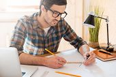 stock photo of concentration man  - Concentrated young man drawing while sitting at his working place - JPG