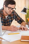pic of concentration man  - Concentrated young man using compass for drawing while sitting at his workplace - JPG