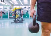 pic of kettlebell  - Closeup of athletic man holding black iron kettlebell in a crossfit training on fitness center - JPG