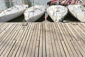 foto of jetties  - Four small learning sailing boats in a row in a wooden jetty - JPG