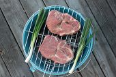 foto of pork cutlet  - Pork cutlets with spring onions on barbecue - JPG