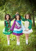 picture of cross-dress  - Three young beautiful girls in irish dance dress and wig posing outdoor - JPG