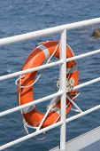 pic of passenger ship  - Orange colored lifebelt and rope hang on a white banister a passenger ship - JPG