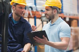 image of warehouse  - Smiling warehouse workers talking together in warehouse - JPG
