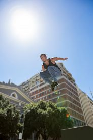 picture of parkour  - Athletic man doing parkour in the city on a sunny day - JPG
