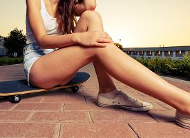 picture of short legs  - Legs of skateboarder girl sit on the board in short jeans shorts place for text is on the ground - JPG